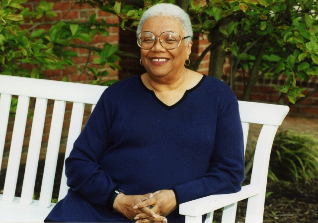 Lucille Clifton sitting on a bench outside with her hands clasped on her lap