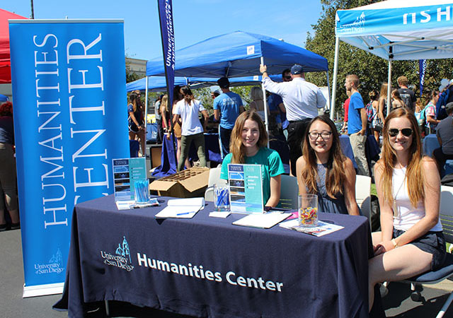 Three students sitting by a Humanities Center banner outside during Alcala Bazaar