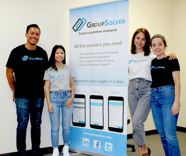 USD alumni smile in front of GroupSolver sign