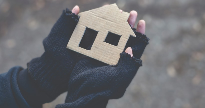 two hands holding a cardboard house
