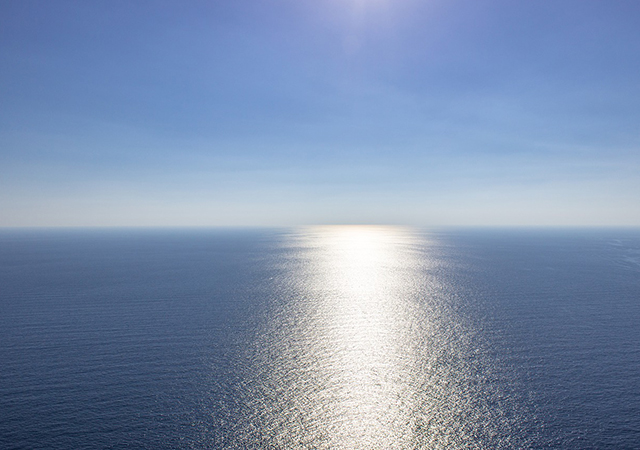 sun reflecting onto the ocean with the blue horizon in the background