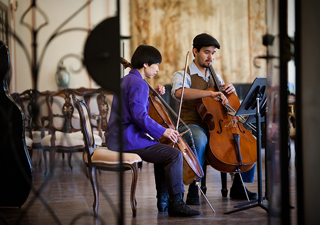 Student and teacher playing cellos