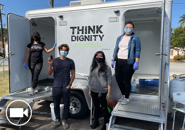 Image of Think Dignity team standing in front of the mobile showers