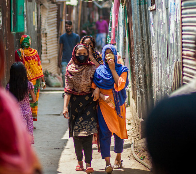 Two young girls in masks walking in Bangladesh