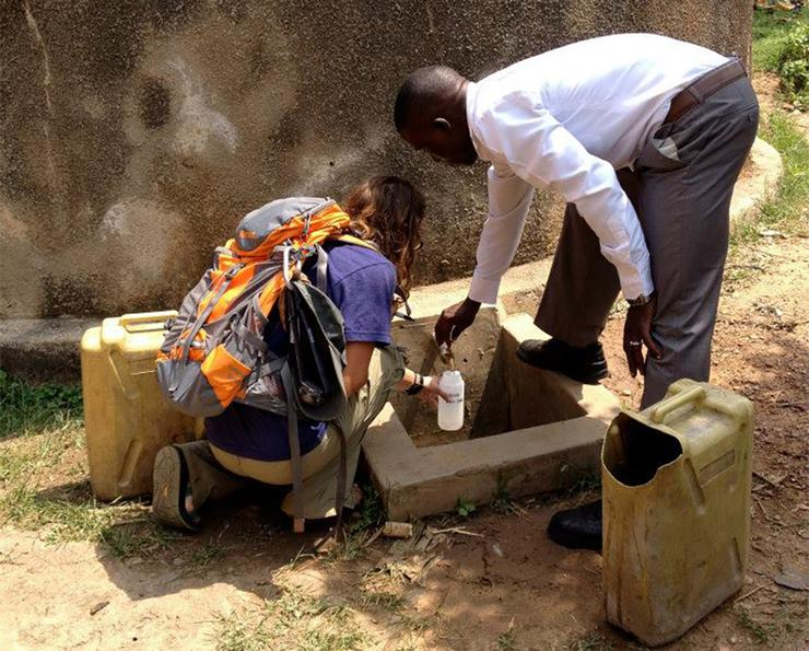 USD faculty and students have spent the last decade working on a project to help provide clean water in Uganda. Here, a USD student from a past trip works with an Uganda student to get a water sample.