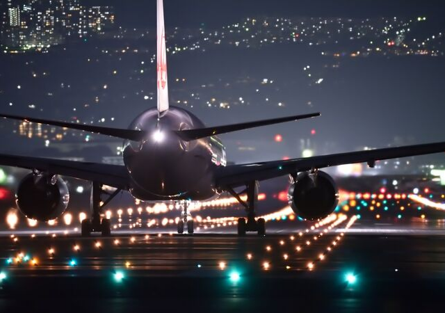 Airplane on a runway at night with lights in the background