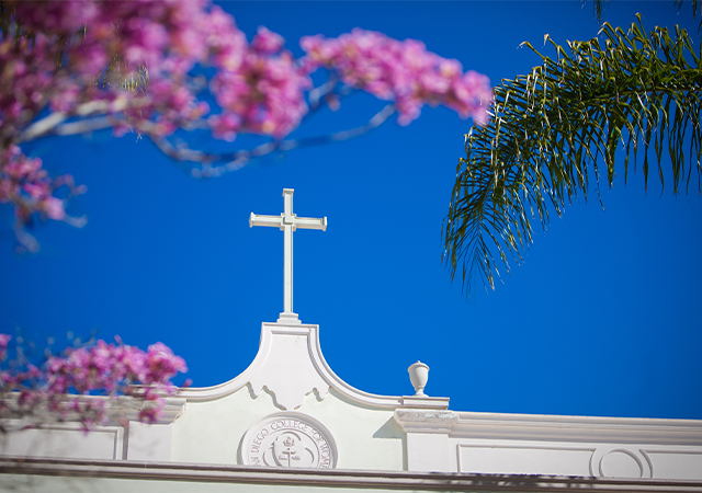 Image of a cross on a USD building with trees with pink blossoms in the foreground