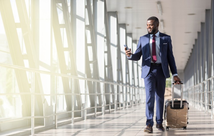 A smiling man in a suit and tie and pulling a suitcase walks past sunny windows in an airport terminal, checking his phone.