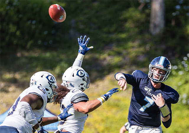 San Diego quarterback Reid Sinnett (7) passes the ball ahead of two UC Davis defenders during a recent USD football game.