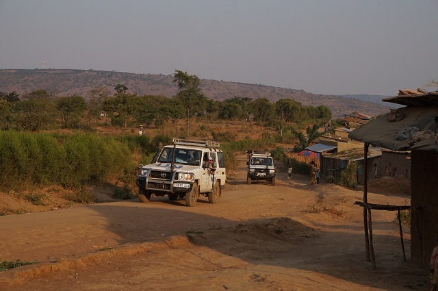 UN jeeps drive through a rural area of Uganda