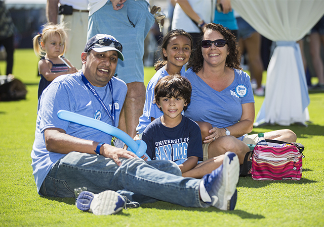 Torero parents sitting on the grass with kids