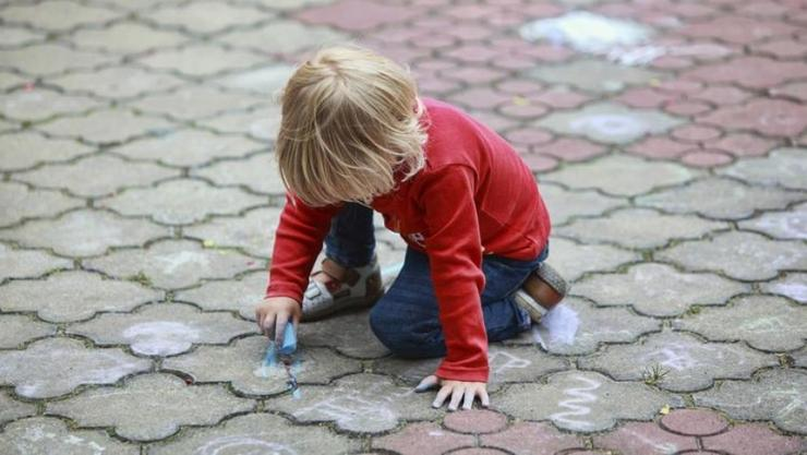 Little kid in red sweater coloring with chalk on the ground