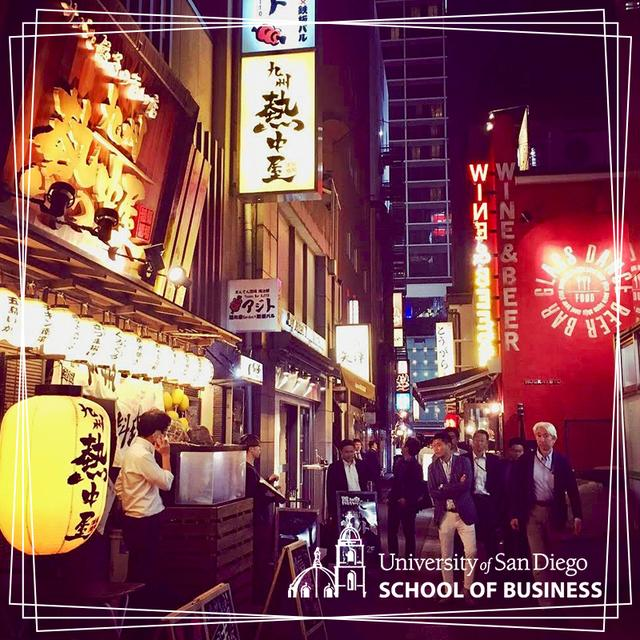A Tokyo street lit up at night with neon signs