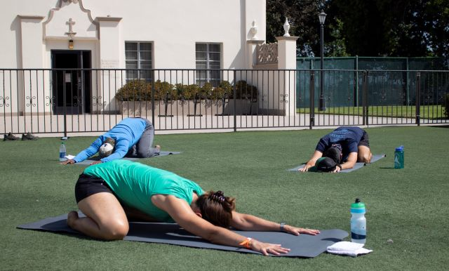 2 yoga participants doing outdoor yoga with an instructor