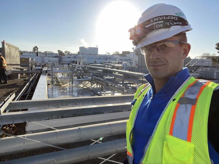 Ian Western (MBA student at the University of San Diego) wears a hard hat at his internship with Siemens