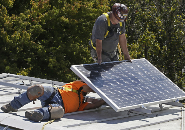 Workers installing solar panels
