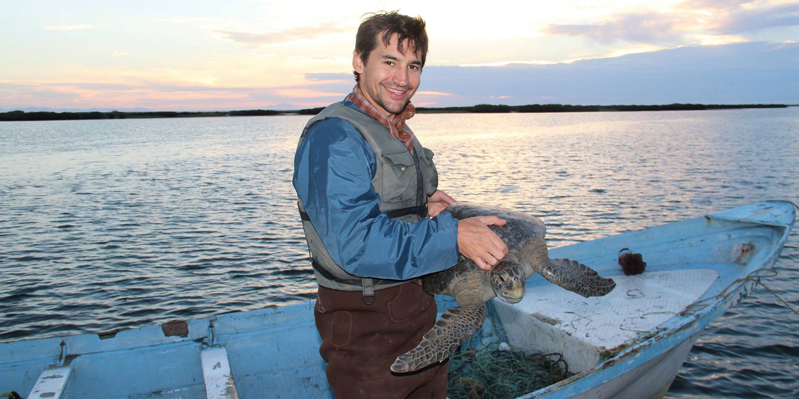Travis Kemnitz holding a sea turtle on a small fishing boat