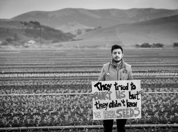 Photograph of immigrant holding a sign