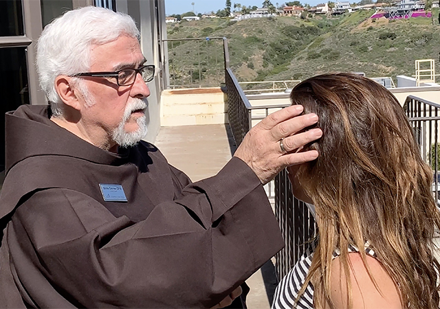 Father Gino Correa administers a symbolic ash cross onto the forehead of Regina Bernal outside of Salomon Hall on Ash Wednesday.