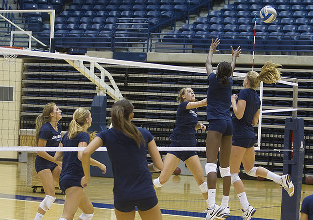 Female USD athletes spiking a volleyball on the court.