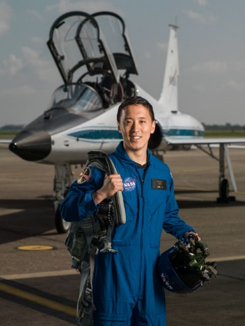 Johnny Kim smiling with aircraft in the background