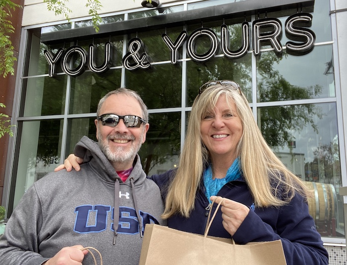 Professor of Supply Chain Management Simon Croom and Assistant Director of Alumni Relations Bridget Breitenberg outside of USD alumni-owned distillery, You&Yours, with their take-out order
