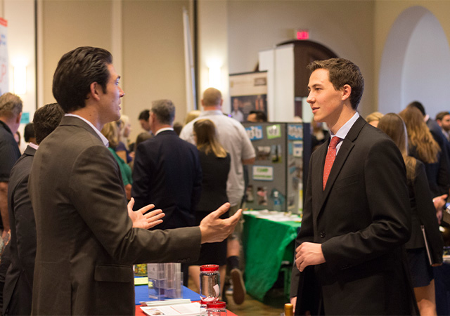 Photo of a student talking to a company representative at the 2016 Career Fair
