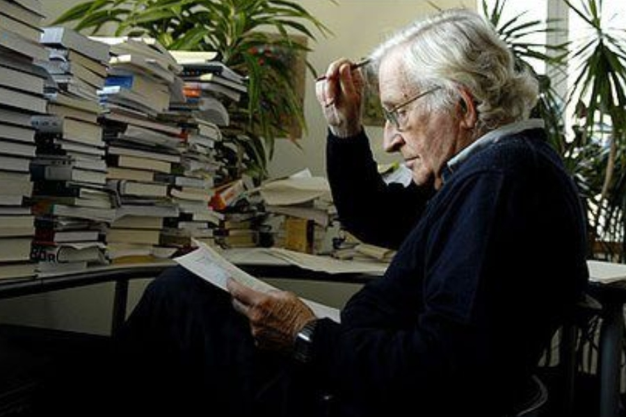 Noam sitting in a chair, reading a book, in front of a desk piled high with books. There is a potted plant in the background.