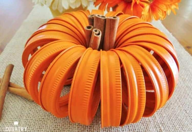 Decorative pumpkin made of metal mason jar rings painted orange