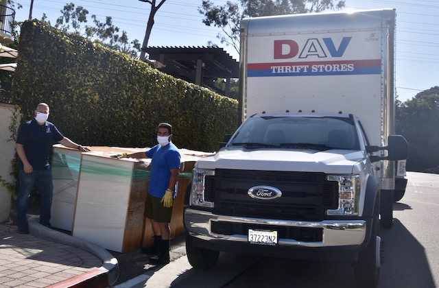 Two men posing with furniture by DAV moving truck