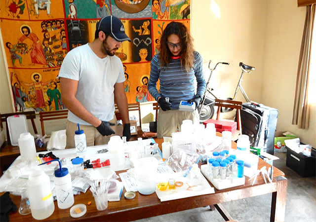 Students on a past trip to Uganda work on water samples in a makeshift lab.