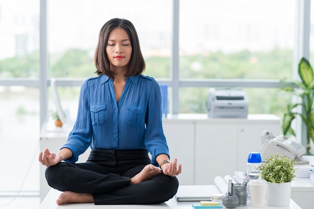 A woman meditating on her desk.