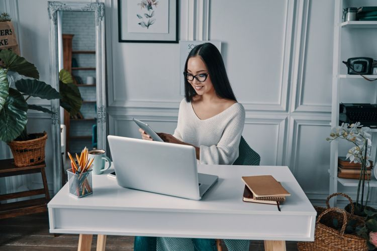 A woman works at home while sitting at her desk