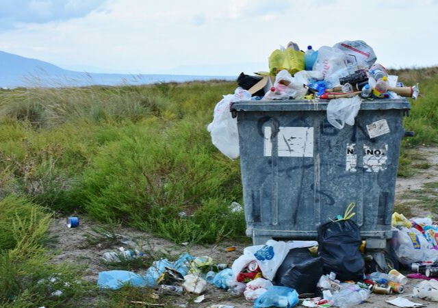 Picture of Recycling and Garbage strewn about a field