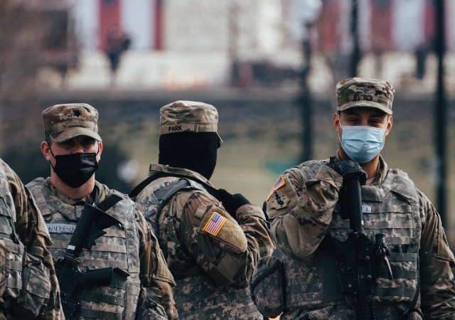 National Guards wearing face masks and standing armed in front of the US capitol building