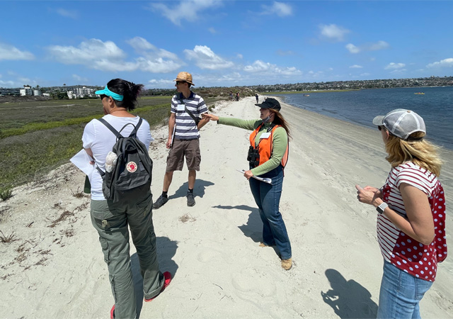 Image of faculty members at the marsh reserve, discussing water justice challenges