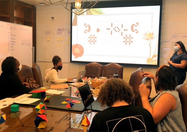 Students and faculty working in a conference room on the MathSpark project