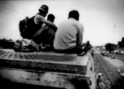 Migrants sitting on train car