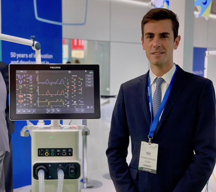 Patricio Keegan, global director of marketing at Tecme, stands with one of Tecme's ventilators