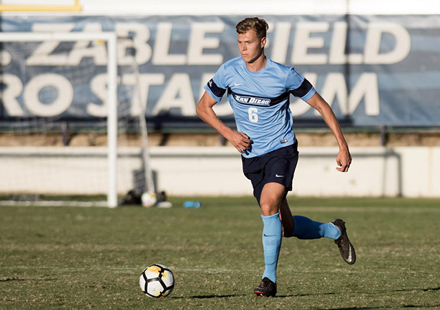 USD soccer player dribbling a ball