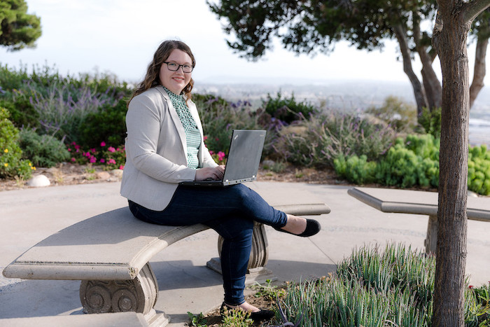 A university of san diego school of business student sits on campus with her laptop
