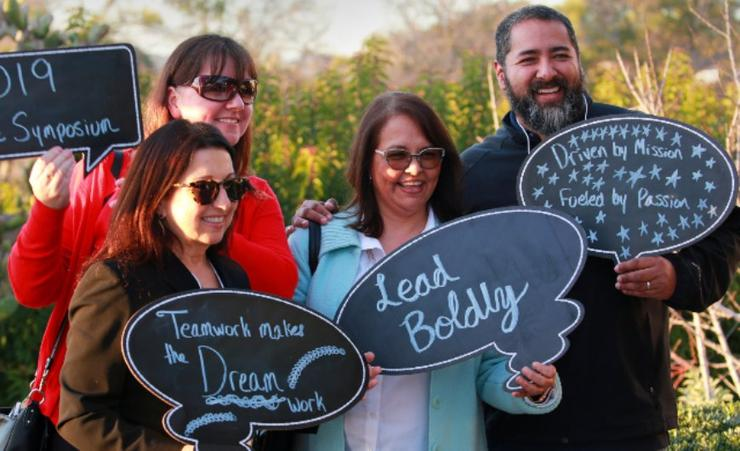 Four smiling people holding chalkboard signs with inspiring messages