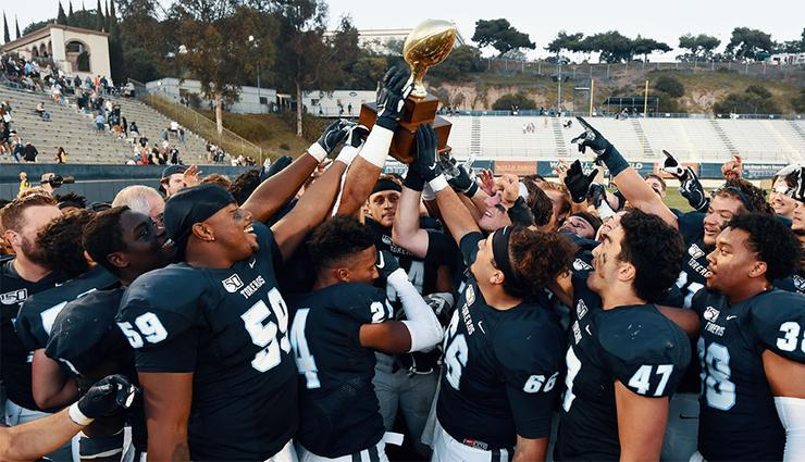 Players celebrate USD's sixth straight Pioneer Football League championship following Saturday's 52-20 home victory over Morehead State. USD is now 8-2 overall, 7-0 in PFL play.