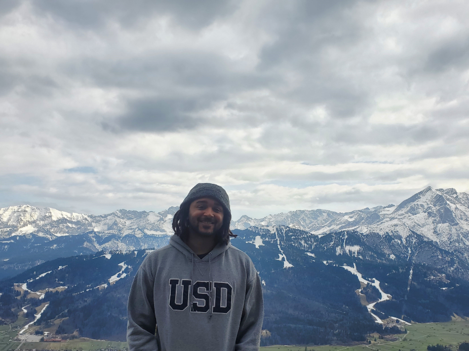 Kyle with USD sweater/mountains