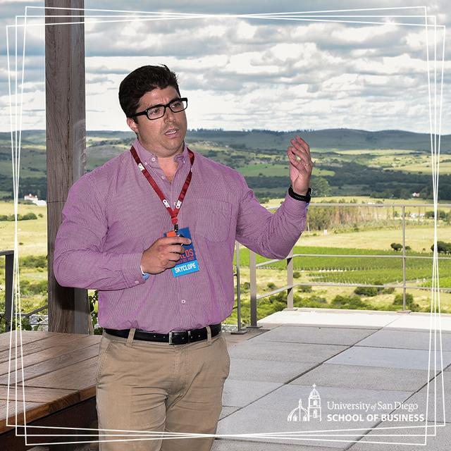 A member of SkyClope pitches their startup idea in front of an audience with a backdrop of the rollings hills of a vineyard in Uruguay
