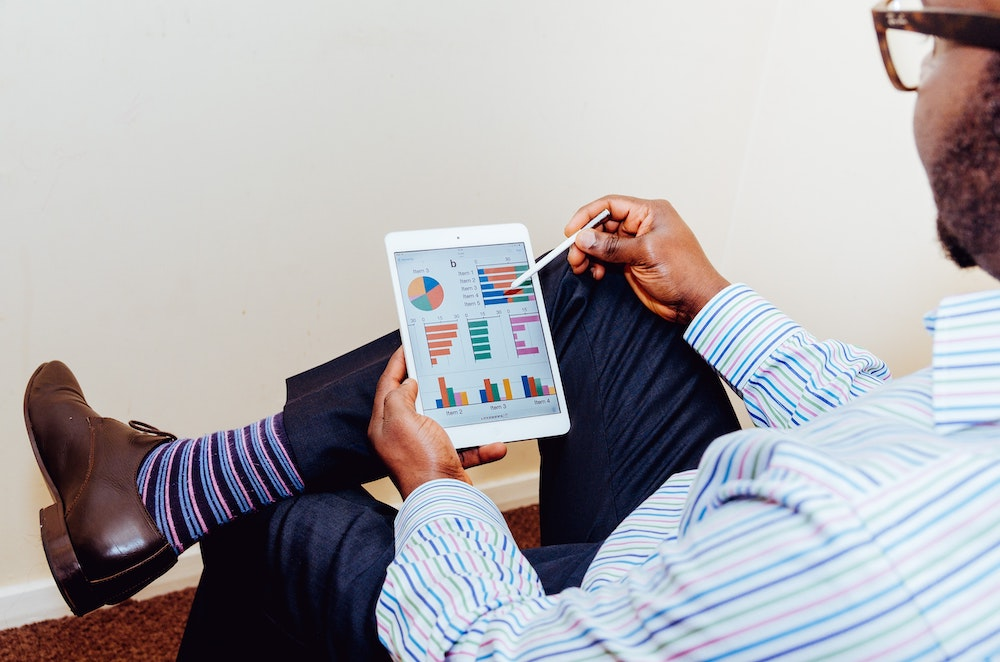 Man looking at marketing analytics on a tablet.