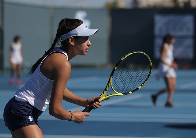 USD women's tennis player about to swing