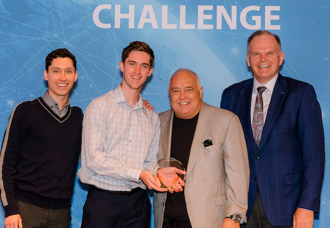 Ron Fowler and USD President James T. Harris III stand with student winners at the 2019 Fowler Global Social Innovation Challenge.