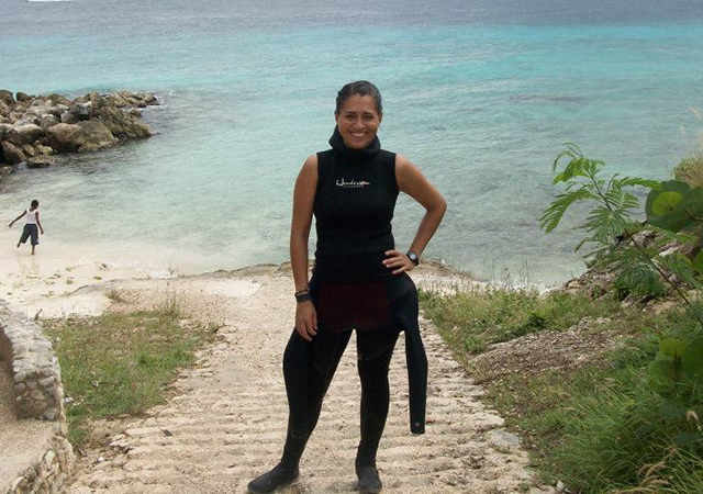 Dr. Brito-Millan stands at the beach wearing a wet-suit.