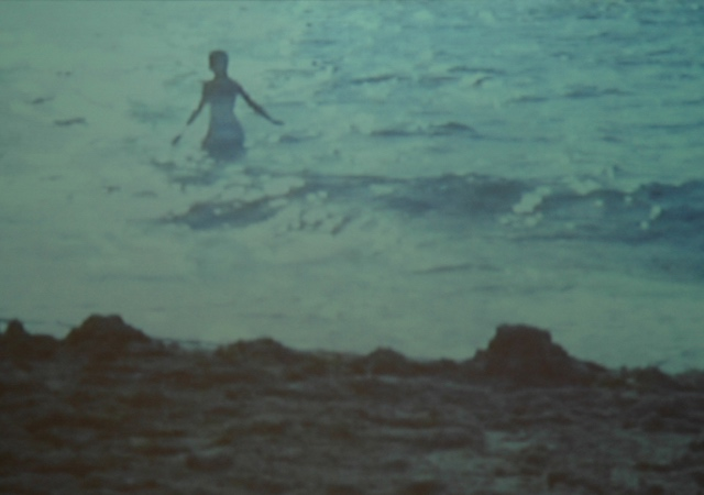 "Frame of ""Amazing Grace"" depicts a woman in clothing walking into the green ocean"